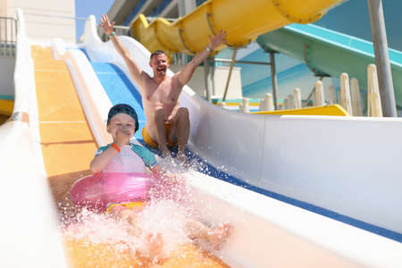 Funny dad and daughter ride water slides. Family spend time at aquapark.