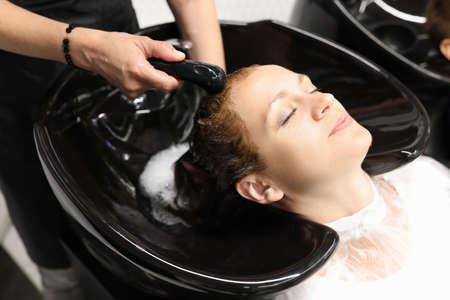 Woman threw her head back into sink in hairdresser. Hairdresser rins hair dye with shower. Archivio Fotografico