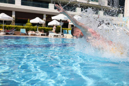 Man swim with breast stroke in blue pool of clear water. Splashes of water fly to sides. Archivio Fotografico