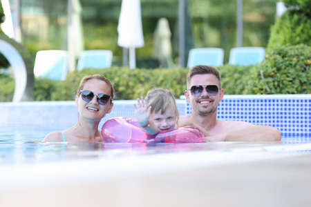 Happy family spend time at sea. Mom dad and daughter swim in pool. Girl with lifebuoy waves her hand.