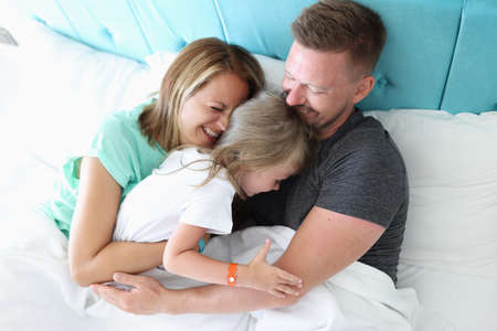 Mom, dad and daughter lie in bed and hug. Happy family spend time together at home.