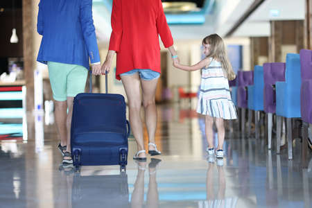 Family leave cafe. Man in blue jacket with his wife in red jacket are carrying suitcase by handle. Woman lead her daughter by hand. Girl in striped dress walk and turn back. Imagens
