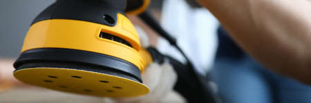 Close-up of persons hands polishing ground with grinding machine. Bright yellow sander instrument and craftsman on construction site. Protective gloves for work. Renovation concept Stock fotó