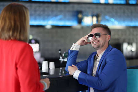 Smiling man in sunglasses sits at bar near woman. Meeting and flirting in clubs concept
