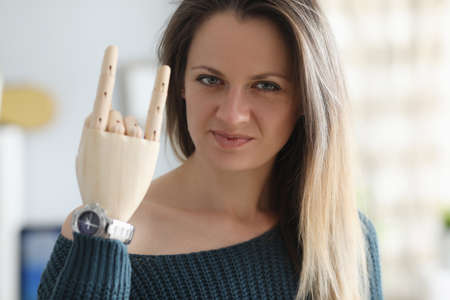 Disabled young woman shows wooden denture gesture portrait. Prosthetics of limbs with perfect working prostheses concept.