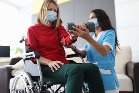Physiotherapist doctor in medical mask helps to raise dumbbell to disabled woman in wheelchair at home portrait. Rehabilitation of disabled people at home during epidemic and coronavirus infection concept. Stock Photo