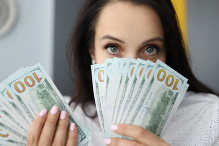Young businesswoman is holding many american dollars in her hands, covering her face. Disbursement of loans social guarantees concept. Stock Photo
