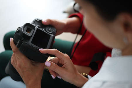 Female friends are looking at photographs on camera close-up. Home photo session concept.