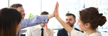 Portrait of biz people performing friendly gesture in order to celebrate important business event. Gorgeous woman doing high five in big modern office. Company meeting concept Reklamní fotografie