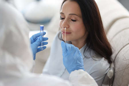 Doctor laboratory assistant in protective suit takes swab from nose of sick patient at home. Laboratory tests for coronavirus concept.