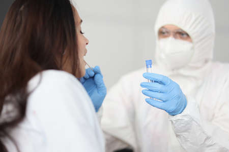 Doctor in white antiplague suit takes swab from his throat with cotton swab into test tube in apartment. Diagnostics testing of patients covid 19 concept. Stock Photo