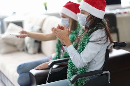 Woman in red cap and jewelry around her neck in wheelchair and face shield claps hands with her friend with tv remote control. Celebrating new year and christmas at home self isolation concept.