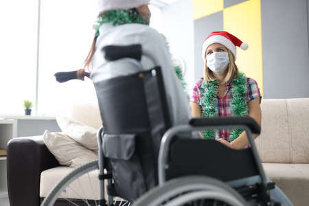 Woman in santa claus hat and with tinsel around her neck wearing protective mask on her face communicates with her friend in wheelchair. Celebrating christmas holidays in rehabilitation center concept.