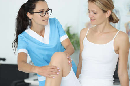 Woman traumatologist doctor in blue suit holds young patient by knee in clinic office portrait. Rehabilitation after leg pearl injury concept.