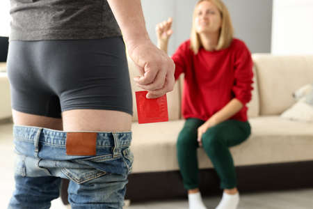Man in shorts pulling jeans down stands with condom in hand close-up in front of girl. Plastic surgery penile enlargement phalloplasty concept.