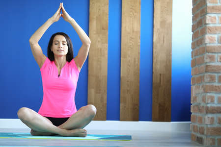 Woman in sportswear sits on boot in an asana pose. Relaxation and stress relief through yoga concept
