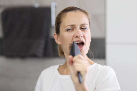 Woman holds comb in her hands and sings in front of mirror. Morning energy boost for the whole day concept Stock fotó