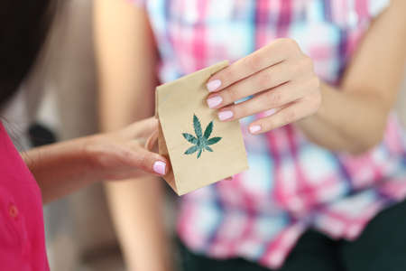 Woman give to buyer paper bag of drugs. Marijuana leaf close-up on paper bag.