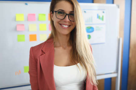 Smiling businesswoman stands in office behind on white board charts with business figures. Conducting business conferences concept 版權商用圖片