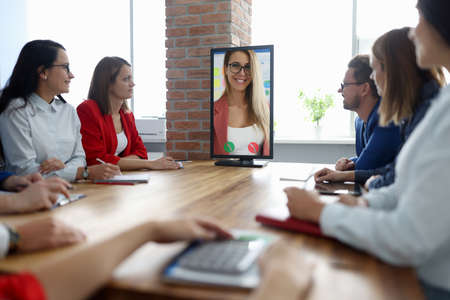 Business people sit at table at meeting and look at monitor with the businesswoman. Online conferences and webinars concept