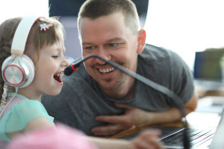 Man smiles and looks at little girl who is playing with headphones at computer. Learning by developing games at the computer concept