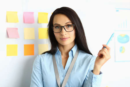 Woman in glasses with pen in her hands stands next to white board. Conducting presentations concept