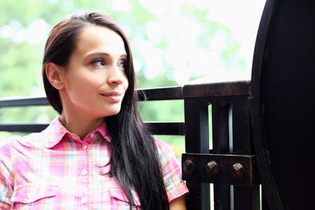 Portrait of brunette woman sitting on summer veranda and dreamily looking into distance. Positive affirmations to lift your mood concept