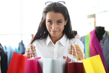 Portrait of young beautiful woman holding multicolored bags with purchases in store. Shopaholism as a mental disorder concept