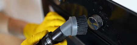Close-up of male hands in yellow gloves vacuuming cookstove handle with special vacuum cleaner after setting. New modern cooker. Renovation and furniture change concept