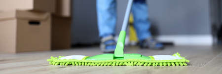 Close-up of male hands holding microfiber fluffy rag and mopping floors. Cleaning apartment after moving or renovation. Housework and spring-cleaning concept