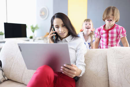 Businesswoman sits on couch with a laptop in background children play. Combining work and family effectively concept
