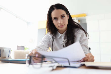 Serious woman is sitting in office at table and holding documents. Working hours and control over the execution of tasks in business concept