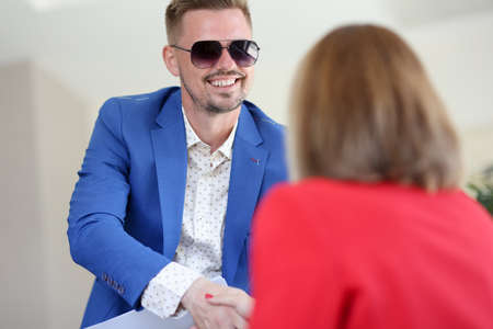 Smiling businessman in sunglasses shakes hands with woman in friendly handshake. Successful business arrangement concept