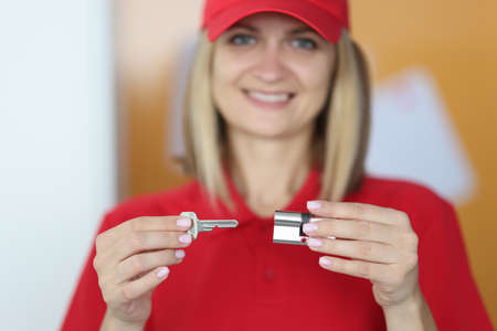 Master holds lock and key in his hands. Lock picking service concept Stock Photo