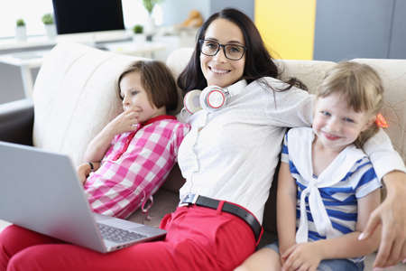 Smiling woman is sitting on sofa with girls. Home pastime with children concept