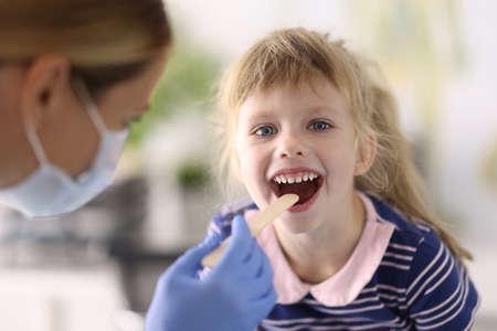 Doctor wearing protective mask examines throat of little girl. Throat disease in children concept