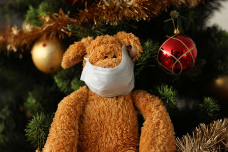Soft toy in protective mask on face hangs on Christmas tree at home close-up. Celebrating New Year in children with leukemia concept Standard-Bild