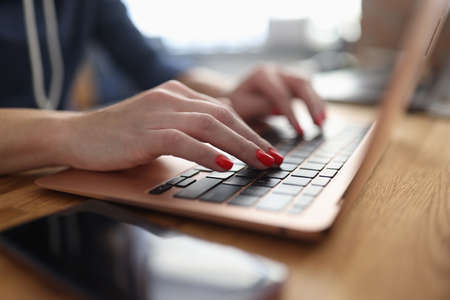 Business woman with red manicure is typing on laptop keyboard at table in office closeup. Remote homework concept. Imagens
