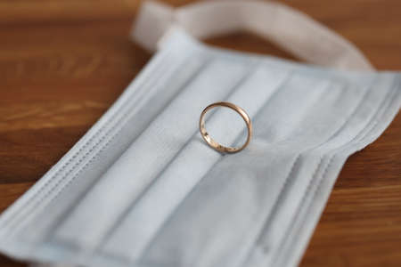 Wedding ring is on protective medical mask. Increase in divorces after quarantine concept