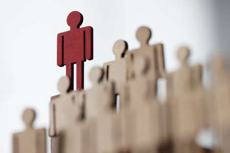 Wooden men stand in row at top one red color. Leadership and uniqueness in the modern world concept
