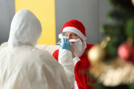 Doctor in protective suit measures temperature of man in santa claus suit. New year and christmas celebration in coronavirus pandemic concept