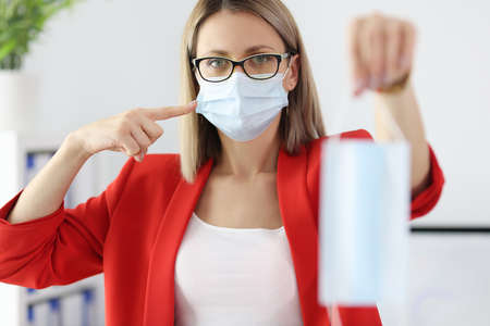 Businesswoman in red suit holding medical protective mask in office. Mask compliance during covid-19 concept