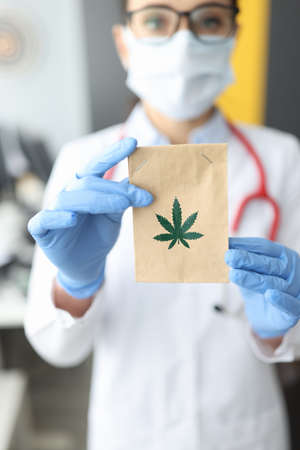 Doctor in rubber gloves holding paper bag with marijuana in clinic closeup. Treatment of cancer with narcotic drugs concept Stok Fotoğraf