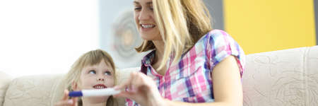Mom and daughter are smiling and looking at pregnancy test. Family replenishment concept
