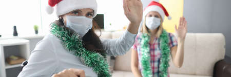 Disabled woman in wheelchair in red santa claus hat waves her hand against background of her friend. Carrying out new year holidays in rehabilitation centers during covid 19 pandemic concept.