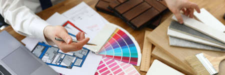 Male hands above table on which samples of finishing materials and color schemes are located. Interior designer concept services