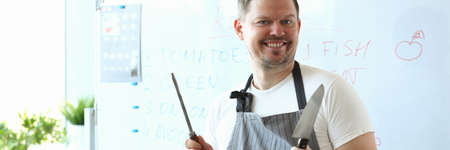 Handsome young man looking at camera and smiling while standing near whiteboard with recipe
