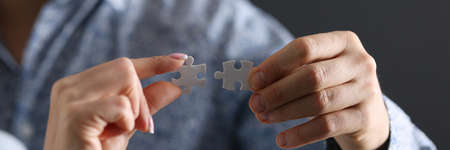 Mans and a womans hand connecting two puzzle pieces closeup. Resolution of family conflicts concept