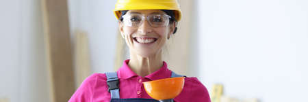 Smiling woman in yellow hard hat and goggles holding plunger in hand. Services of woman plumbing concept Foto de archivo