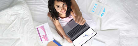 Top view of smiling happy female showing thumbs up. Young attractive woman working from home. Sweet lady with laptop and papers in bed. Remote job and freelance concept